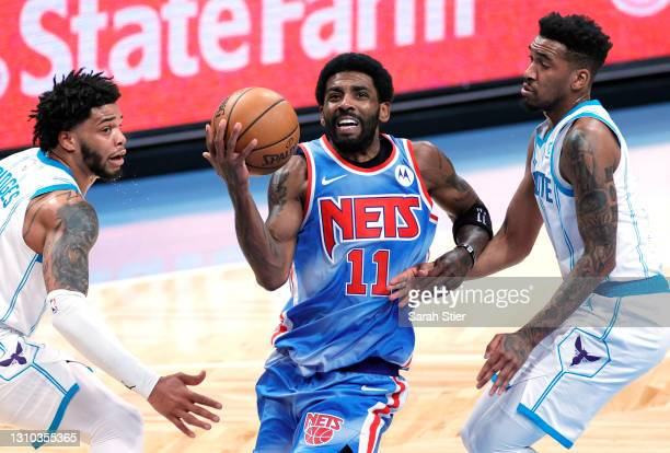 Kyrie Irving of the Brooklyn Nets dribbles as Miles Bridges and Malik Monk of the Charlotte Hornets defend during the first half at Barclays Center...