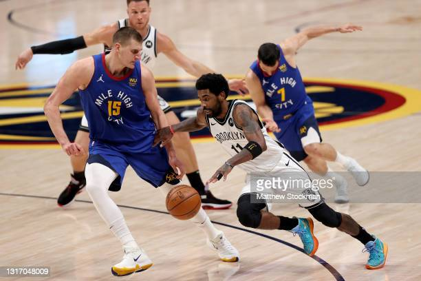 Kyrie Irving of the Brooklyn Nets drives against Nikola Jokic of the Denver Nuggets in the third quarter at Ball Arena on May 08, 2021 in Denver,...