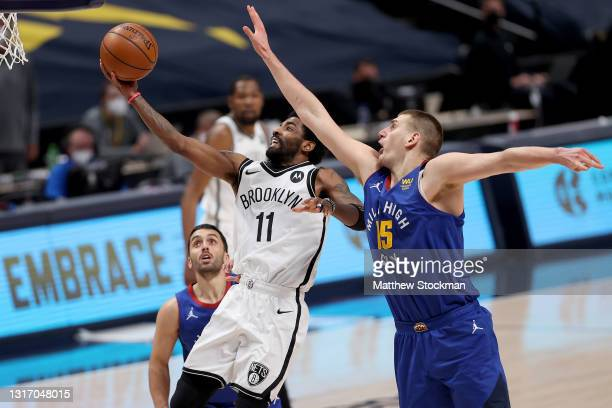 Kyrie Irving of the Brooklyn Nets goes to the basket against Nikola Jokic of the Denver Nuggets in the third quarter at Ball Arena on May 08, 2021 in...