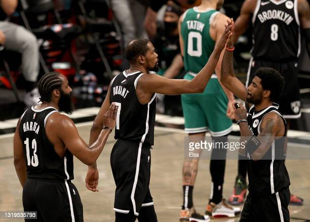 Kyrie Irving of the Brooklyn Nets is congratulated by teammates Kevin Durant and James Harden after Irving drew the foul against the Boston Celtics...