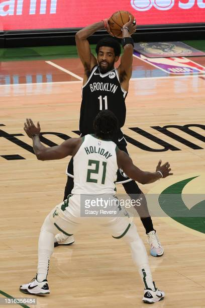 Kyrie Irving of the Brooklyn Nets is defended by Jrue Holiday of the Milwaukee Bucks during the first half of a game at Fiserv Forum on May 04, 2021...