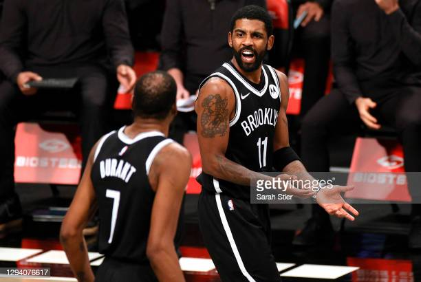 Kyrie Irving of the Brooklyn Nets reacts toward Kevin Durant during the second half against the Atlanta Hawks at Barclays Center on January 01, 2021...