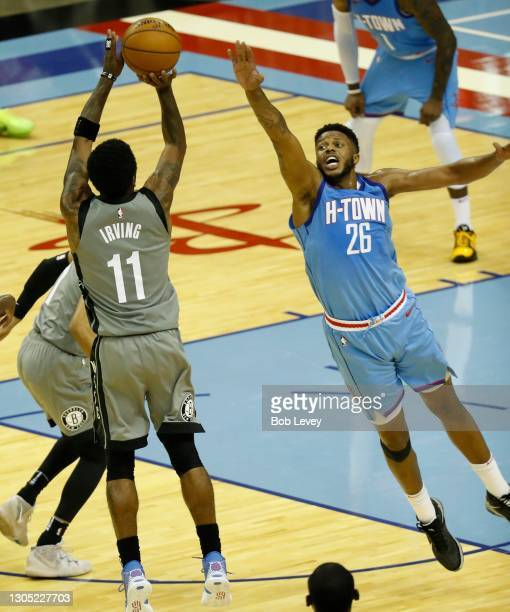 Kyrie Irving of the Brooklyn Nets shoots a three point shot over Justin Patton of the Houston Rockets during the fourth quarter at Toyota Center on...