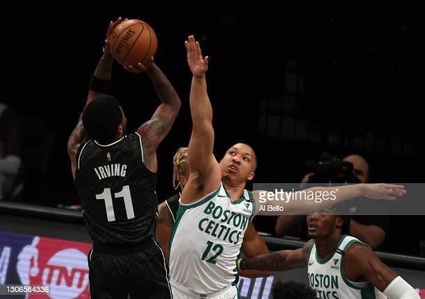 Kyrie Irving of the Brooklyn Nets shoots against Grant Williams of the Boston Celtics during their game at Barclays Center on March 11, 2021 in New...
