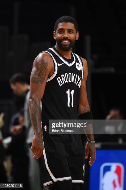 Kyrie Irving of the Brooklyn Nets smiles during a preseason game against the Boston Celtics on December 18, 2020 at the TD Garden in Boston,...