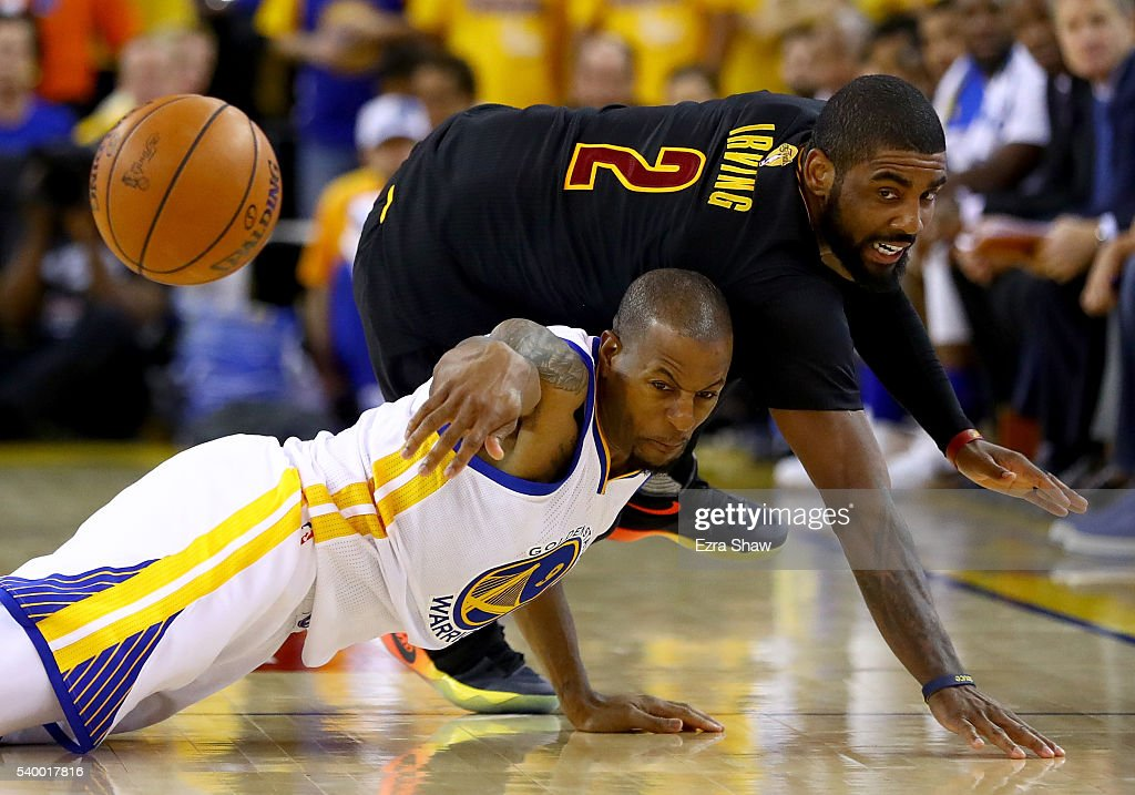 Kyrie Irving #2 of the Cleveland Cavaliers and Andre Iguodala #9 of the Golden State Warriors dive for the ball during the fourth quarter in Game 5 of the 2016 NBA Finals at ORACLE Arena on June 13, 2016 in Oakland, California.
