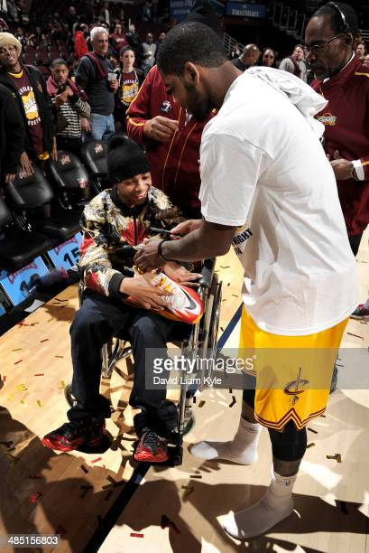Kyrie Irving of the Cleveland Cavaliers autographs his game shoes and gives them to a young fan on Fan Appreciation Night after the game the Brooklyn...