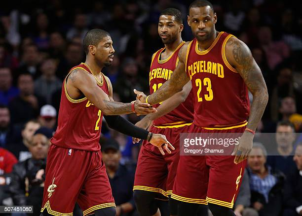 Kyrie Irving of the Cleveland Cavaliers celebrates a first half basket with teammates Tristan Thompson and LeBron James during the first half while...
