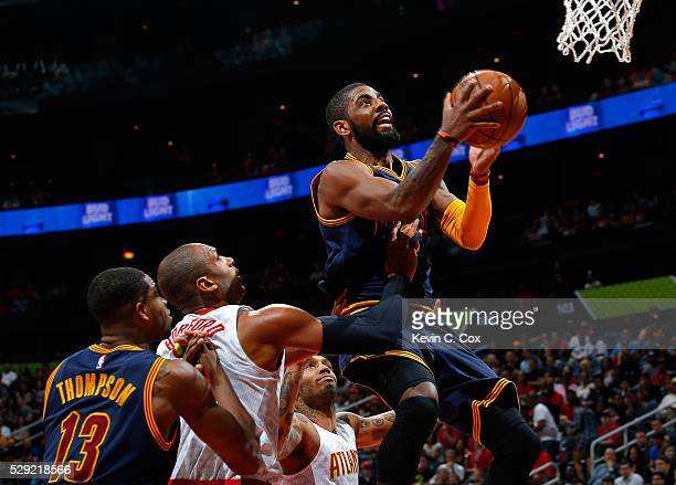 Kyrie Irving of the Cleveland Cavaliers drives the lane against Al Horford and Mike Scott of the Atlanta Hawks in Game Four of the Eastern Conference...