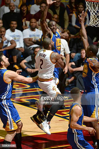 Kyrie Irving of the Cleveland Cavaliers drives to the basket against Draymond Green of the Golden State Warriors during the 2016 NBA Finals Game...