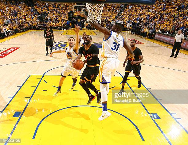 Kyrie Irving of the Cleveland Cavaliers goes to the basket against Festus Ezeli of the Golden State Warriors and Klay Thompson of the Golden State...