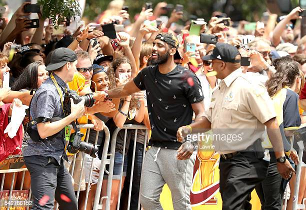 Kyrie Irving of the Cleveland Cavaliers greets the crowd along the route during the Cleveland Cavaliers 2016 NBA Championship victory parade and...