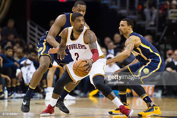 Kyrie Irving of the Cleveland Cavaliers looks for a pass while under pressure from Lavoy Allen of the Indiana Pacers and George Hill of the Indiana...