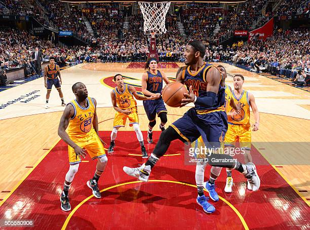 Kyrie Irving of the Cleveland Cavaliers passes the ball in midair against the Golden State Warriors on January 18 2016 at Quicken Loans Arena in...