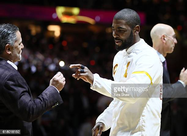 Kyrie Irving of the Cleveland Cavaliers receives his championship ring from owner Dan Gilbert before the game against the New York Knicks at Quicken...