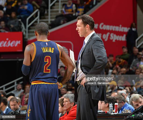 Kyrie Irving of the Cleveland Cavaliers shares a moment with head coach Luke Walton of the Golden State Warriors on January 18 2016 at Quicken Loans...
