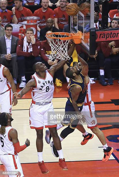 Kyrie Irving of the Cleveland Cavaliers shoots the ball against Bismack Biyombo of the Toronto Raptors and Cory Joseph during the first half in game...
