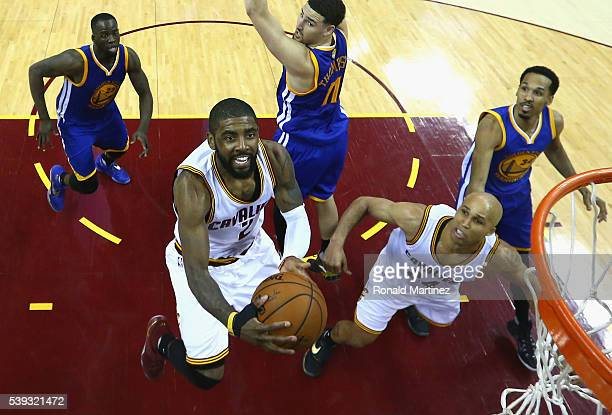 Kyrie Irving of the Cleveland Cavaliers takes a shot in front of Draymond Green Klay Thompson Shaun Livingston of the Golden State Warriors and...