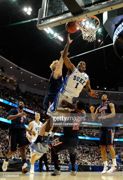 Kyrie Irving of the Duke Blue Devils draws contact against Kyryl Natyazhko and Lamont Jones of the Arizona Wildcats during the west regional...