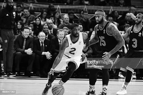 Kyrie Irving of the Eastern Conference dribbles against DeMarcus Cousins of the Western Conference during the 2015 NBA AllStar Game as part of the...