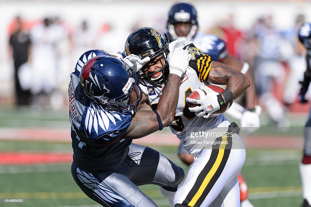 Kyries Hebert #34 of the Montreal Alouettes tackles Bakari Grant #84 of the Hamilton Tiger-Cats during the CFL game at Percival Molson Stadium on September 7, 2014 in Montreal, Quebec, Canada. The Alouettes defeat the Tiger-Cats 38-31.