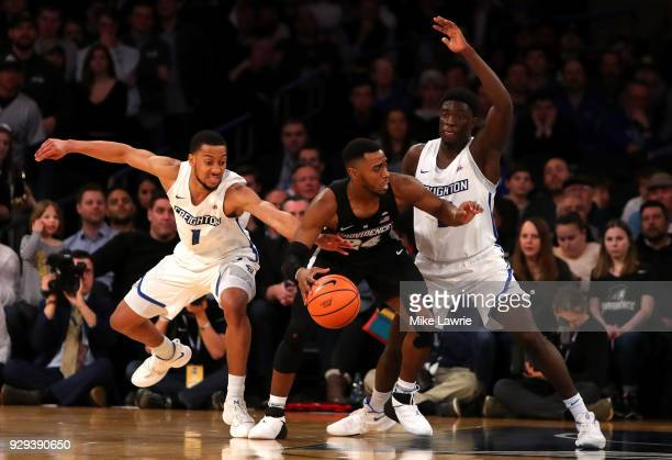 Kyron Cartwright of the Providence Friars handles the ball against Davion Mintz and Khyri Thomas of the Creighton Bluejays in the second half during...