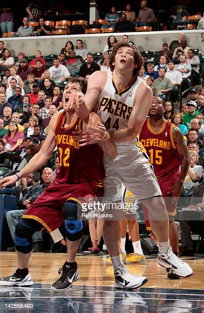 Kyrylo Fesenko of the Indiana Pacers and Luke Walton of the Cleveland Cavaliers play for a rebound during the game on April 13 2012 at Bankers Life...