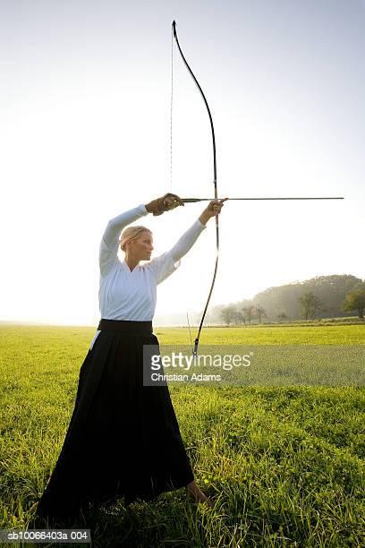 Kyudo player aiming bow and arrow