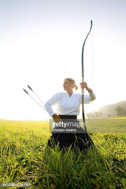 Kyudo player with bow and arrow in field