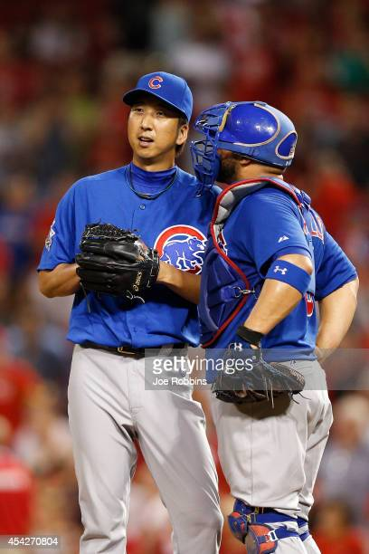 Kyuji Fujikawa and Welington Castillo of the Chicago Cubs talk prior to the seventh inning of the game against the Cincinnati Reds at Great American...