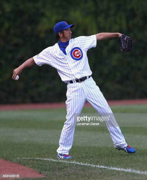 Kyuji Fujikawa of the Chicago Cubs plays catch with an outfielder during a game against the Tampa Bay Rays at Wrigley Field on August 9 2014 in...