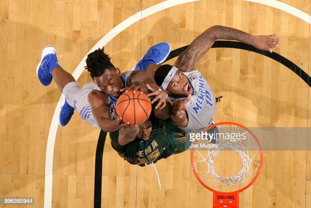 Kyvon Davenport and Mike Parks Jr #10 of the Memphis Tigers jump for a rebound against Sammy Friday of the Siena Saints on December 20 2017 at...