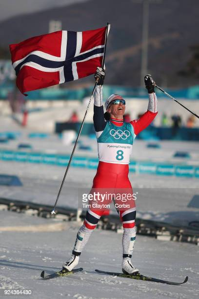 l Marit Bjoergen of Norway celebrates at the finish line while winning the gold medal in the CrossCountry Skiing Ladies' 30km Mass Start Classic at...