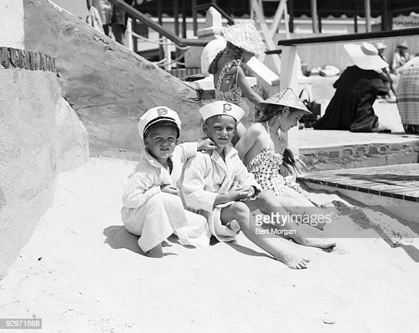 l to r Austin and William Hearst and Deborah Hearst sit on a sandy beach at Southampton LI NY c 1957 The boys wear a captain's hat and sailor cap...