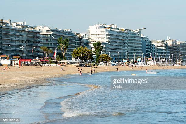 La Baule Escoublac vacationers on the beach of La Baule in summer with buildings along the waterfront