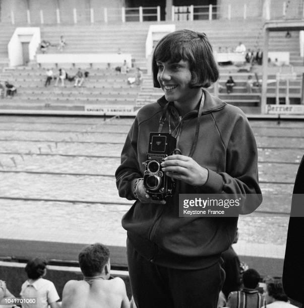 La championne de natation Christine Caron qui a battu le record du 100 mètres dos au stade Georges Vallerey photographie ses parents venus...