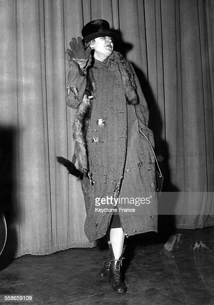 La chanteuse de cabaret et actrice Suzy Delair vêtue d'un costume de scène usagé et d'un chapeau usé répète pour son prochain show sur la scène de...