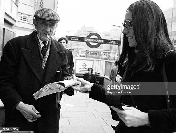 La chanteuse grecque Nana Mouskouri achète un journal à un homme, devant une entrée de station de métro, à Londres, Angleterre, circa 1970.