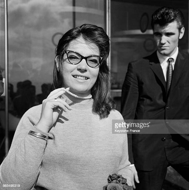 La chanteuse grecque Nana Mouskouri montrant le collier de perles de culture qu'elle a reçu à son arrivée à l'aéroport d'Orly France le 9 octobre 1961