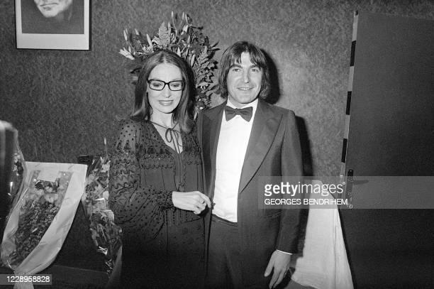 La chanteuse grecque Nana Mouskouri pose après son spectacle, le 17 octobre 1979 dans sa loge à l'Olympia à Paris en compagnie du chanteur français...