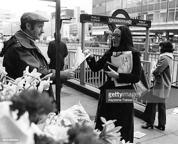 La chanteuse grecque Nana Mouskouri un journal dans les bras achète à un fleuriste un bouquet devant une entrée de station de métro à Londres...