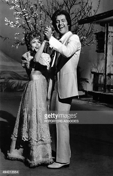 La chanteuse Mireille Mathieu en robe longue et le chanteur Joe Dassin en costume blanc chantent et dansent pour une émission de télévison circa 1960...