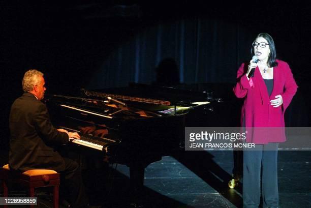 La chanteuse Nana Mouskouri interprète une chanson à l'issue du spectacle du comédien Jean-Claude Brialy, le 19 juin 2004 dans la salle Coppélia de...
