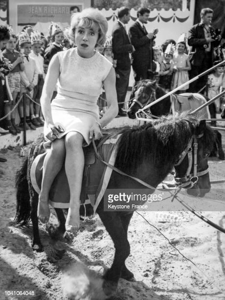 La comédienne Colette Brosset sur un poney au Parc d'attractions de Jean Richard le 7 juin 1963 à Ermenonville, France.