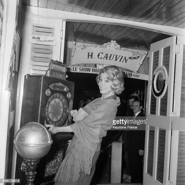 La comédienne Danielle Darrieux essayant sa chance avec une machine à sous dans un cabaret à Nice France le 21 avril 1964