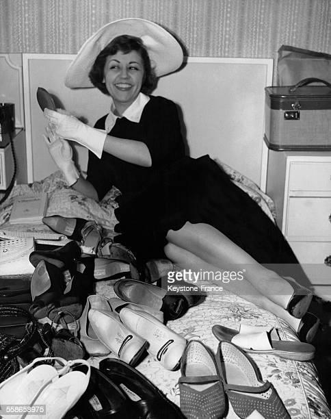 La comédienne et chanteuse de cabaret française Suzy Delair se relaxant dans son hôtel entourée de plusieurs paires de chaussures le 6 juin 1954 à...