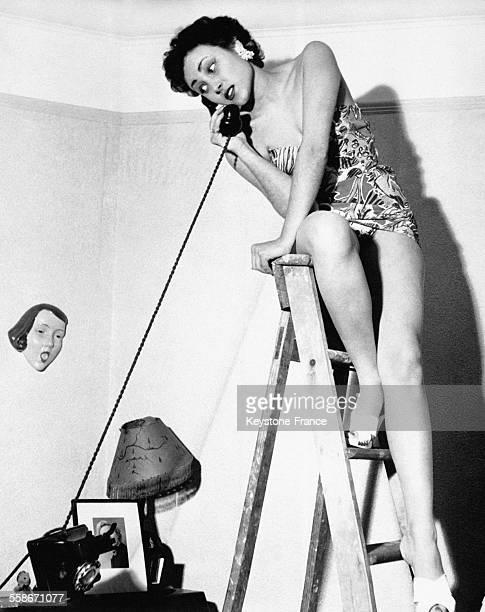 La comédienne francobritannique Pascale Roberts au téléphone perchée sur une échelle circa 1960