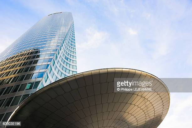 La Defense Paris financial district Tour EDF building with circular shape structure against blue sky and white clouds