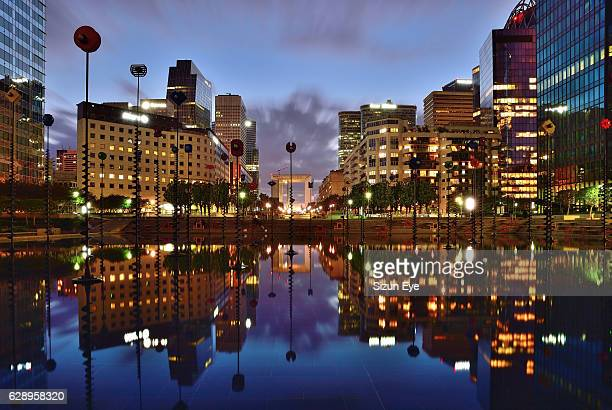 La Défense, the business district of Paris with reflections in Takis Basin at blue hour in France.