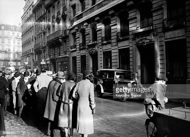 La foule de curieux stationnant devant l'immeuble ou se trouve la Compagnie d'assurances 'La Confiance' pendant la perquisition le 5 janvier 1934 a...